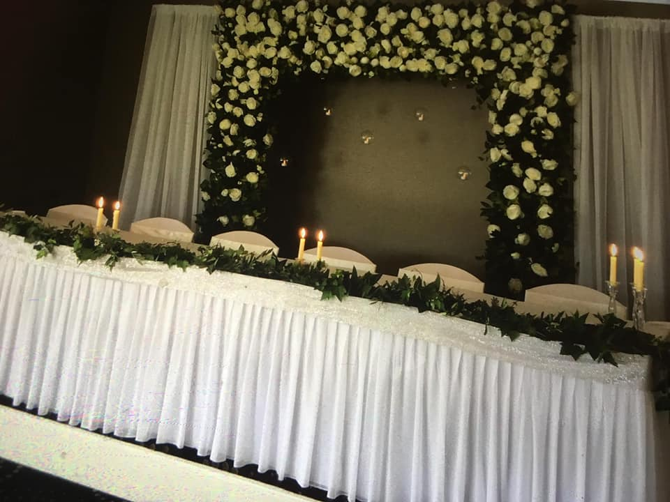 Floral arch with hanging glass with votives and drapery